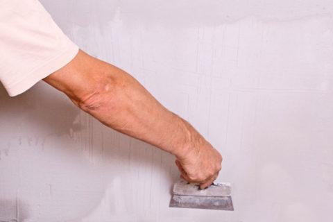 man scraping wall