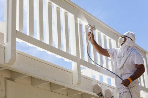 man spraying deck